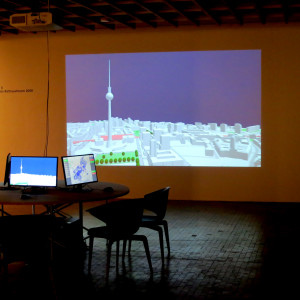 The Enabling DEMO:POLIS installation at Akademie der Künste Berlin. Three workstations for visitors, one of them with a projection screen.
